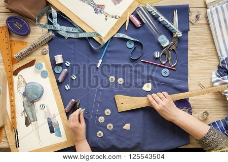 Desk designer fashion. Fashion designer starts cutting fabric to create fashionable clothes on the sketches. poster