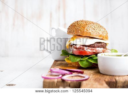 Breakfast set. Homemade beef burger with fried egg and vegetables, onion rings and coffee cups on wooden board, white painted background. Selective focus, copy space