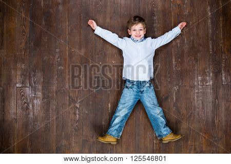 Happy child. Top view creative photo of little boy on vintage brown wooden floor. Boy looking at camera and smiling
