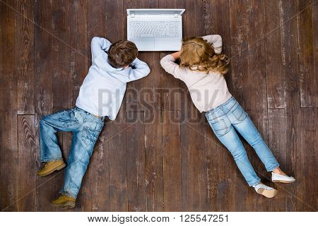 Happy children. Top view creative photo of little boy and girl on vintage brown wooden floor. Children using laptop