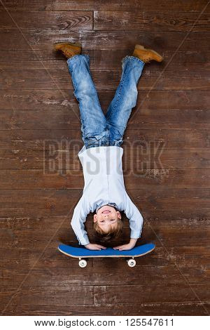 Happy child. Top view creative photo of little boy on vintage brown wooden floor. Boy riding on skateboard on his hands