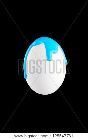 White egg drenched in blue colors on a black background