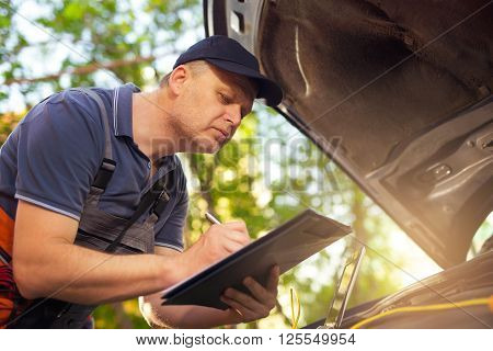 Portrait of a mechanic at w?rk writing on clipboard