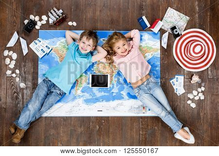 Happy children. Top view creative photo of little boy and girl on vintage brown wooden floor. Children lying on world map near travel things, looking at camera and smiling