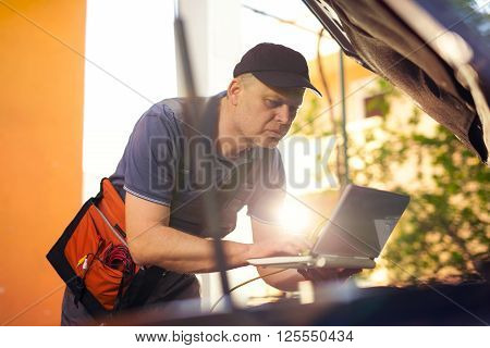 Professional car mechanic working in auto repair service using laptop