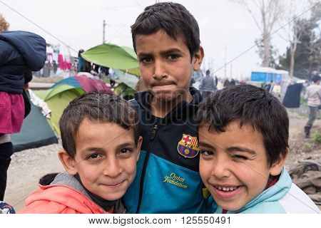 EIDOMENI, GREECE - MARCH 17, 2015: Three boys from Syria pose near their tent on March 17, 2015 in the refugee camp of Eidomeni, Greece. For several weeks more than 10.000 refugees and immigrants wait here for the borders to open.