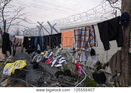 EIDOMENI, GREECE - MARCH 17, 2015: Refugees and immigrants try to dry their clothes after heavy rain on March 17, 2015 in the refugee camp of Eidomeni, Greece. For several weeks more than 10.000 refugees and immigrants wait here for the borders to open.