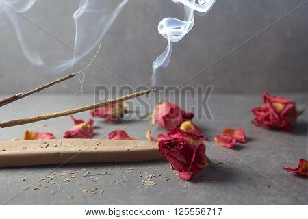 Incense stick. Aromatherapy whit petals on grey background