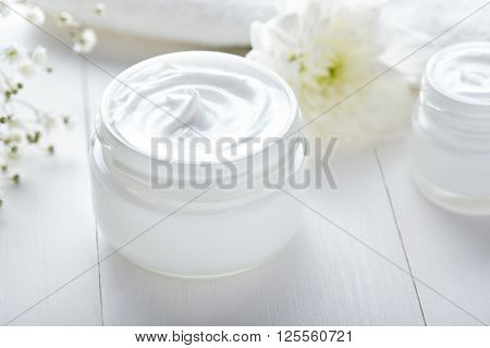 Anti wrinkle cosmetic cream with herbal flowers face, skin and body care hygiene moisture lotion wellness therapy mask in glass jar with towel on white background