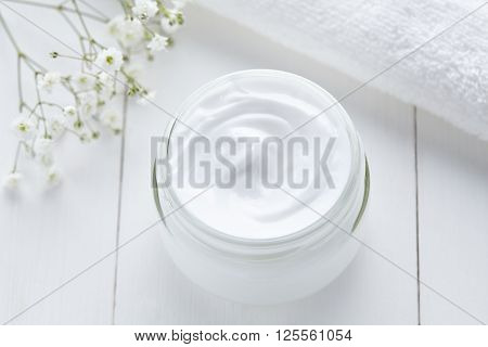 Cosmetic cream natural organic skin, face and body care hygiene moisture lotion wellness therapy mask in glass jar with towel on white background. Top view.