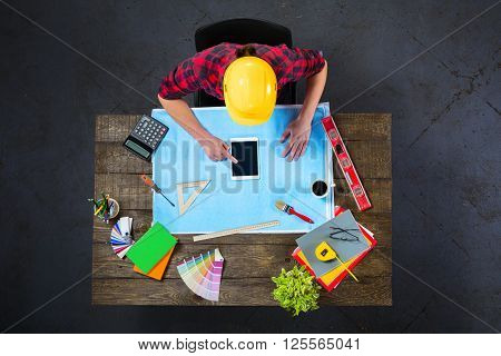 Top view creative photo of engineer sitting at dark wooden vintage table. Architect with helmet working with blueprints and tablet computer