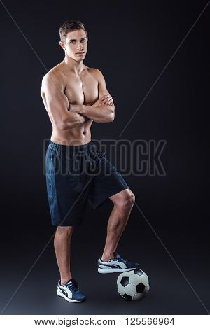 Attractive and muscular football player. Studio shot of young shirtless sportsman on black background. Man with football ball looking at camera