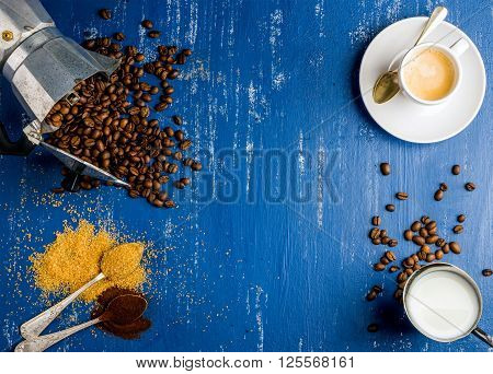 Food frame. Espresso cup, cream, arabika beans in moka pot, brown sugar and ground coffee in spoons on wooden blue painted background. Top view, copy space