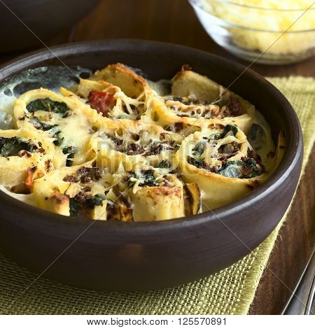 Baked crepe rolls casserole filled with spinach tomato and mincemeat with cream sauce and grated cheese on top served in rustic bowl photographed with natural light (Selective Focus Focus on the front of the middle roll)