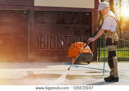 Caucasian Male at Work Cleaning Residential Brick Road Using High Pressure Water Cleaning System Machine