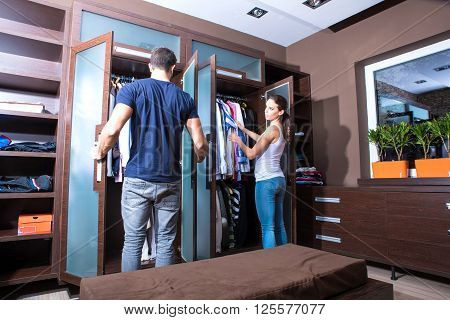 Beautiful young couple looking dresses in the dressing room.