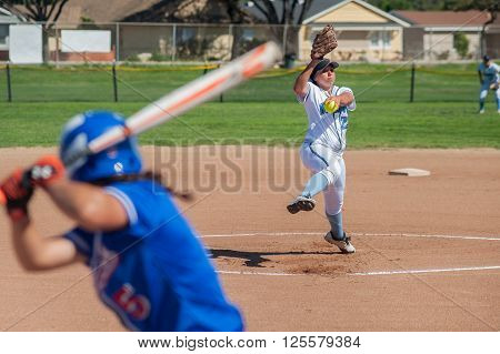 Close up of softball pitcher winding up to throw the curve ball to the batter.