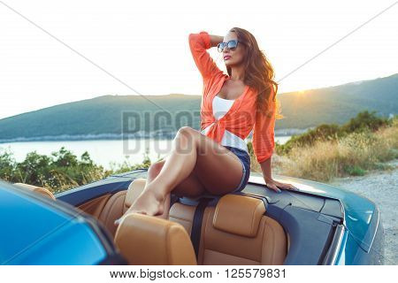 Beautiful woman sitting in cabriolet enjoying trip on luxury modern car with open roof fashionable lifestyle concept