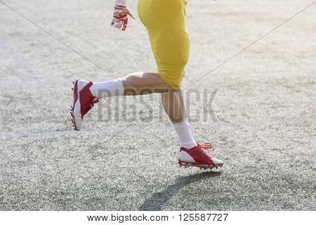Unrecognizable football player running on the green grass court