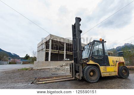 yellow pallet lift truck transporter standing at storehouse