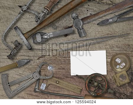 vintage jeweler tools and diamonds over wooden bench, space for your business name
