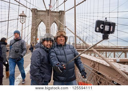 NEW-YORK - CIRCA MARCH 2016: men taking a selfie in New-York. A selfie is a self-portrait photograph, typically taken with a camera phone held in the hand or supported by a selfie stick.