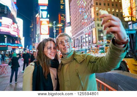 NEW-YORK - CIRCA MARCH 2016: people taking a selfie in New-York. A selfie is a self-portrait photograph, typically taken with a camera phone held in the hand or supported by a selfie stick.