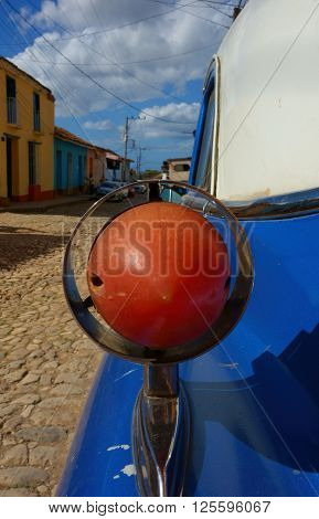 Rear light of a classic American car on street in Trinidad, Cuba on sunny day in December 2013.