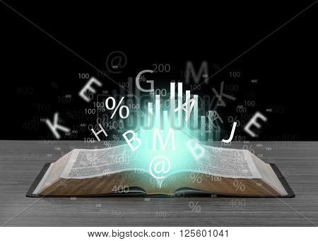 Letters and numbers flying off book on wooden table over black background
