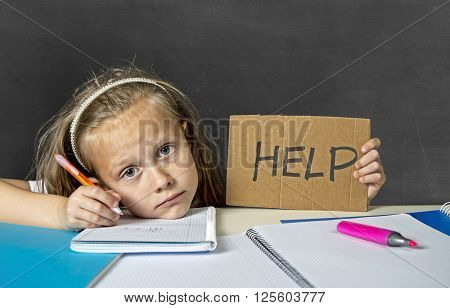 sad and tired cute junior schoolgirl with blond hair sitting in stress working doing homework looking bored and overwhelmed in children education at school and low academic performance poster