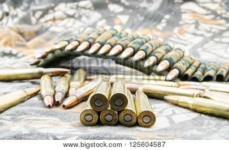 Hollow-point ammunitions for rifle on camouflage background.