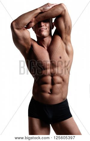 Young muscular bodybuilder posing over white background.