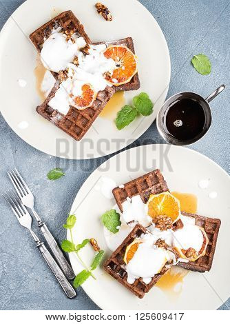 Belgian soft waffles with blood orange, cream, marple syrup and mint  on white plates over concrete textured background. Top view