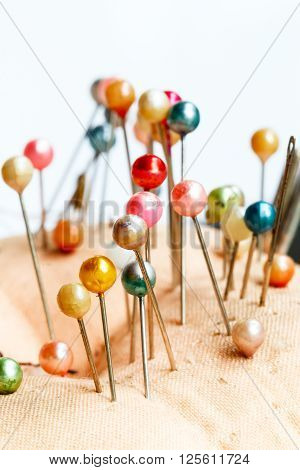 Fabric pincushion with colorful pins on white background