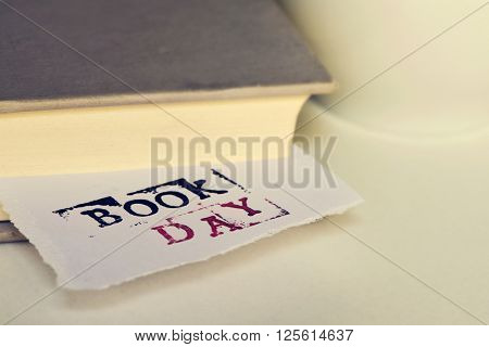closeup of a a piece of paper wit the text book day popping up from a book, placed on a white table next to a cup of coffee or tea