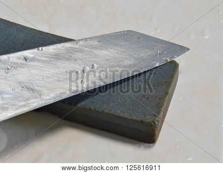 kitchen knife blade and whetstone on tile floor
