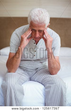 Tensed senior man with head in hands while sitting on bed