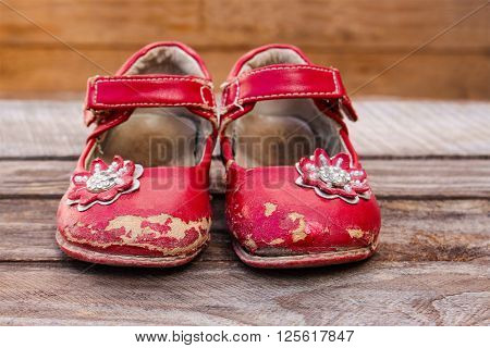 Old red baby shoes on wooden background.