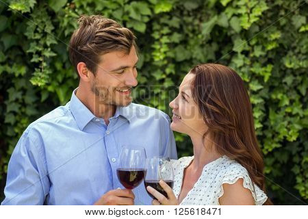 Romanic couple looking at eachother while holding wineglasses at front yard