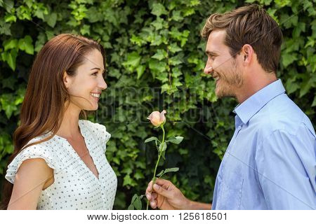 Happy man giving rose to woman at front yard