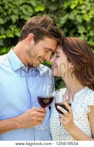 Romanic couple holding wineglasses with eyes closed at front yard