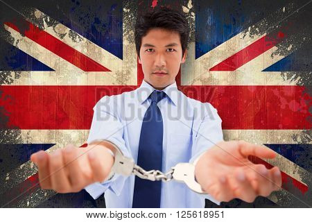 Businessman with handcuffs against union jack flag in grunge effect