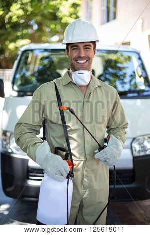 Portrait of confident worker with pesticide sprayer while standing by van