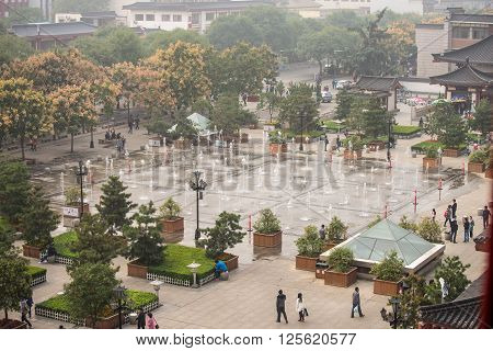 Xian China - October 16 2013: Local people and tourists walk around the Music fountain in the square of Dayan pagoda Xian China. Misty day.