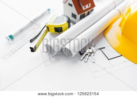 architecture, building, construction, real estate and home concept - close up of architectural blueprint with tools and house keys