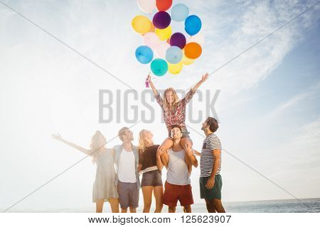 Portrait of friends holding balloon on a sunny day