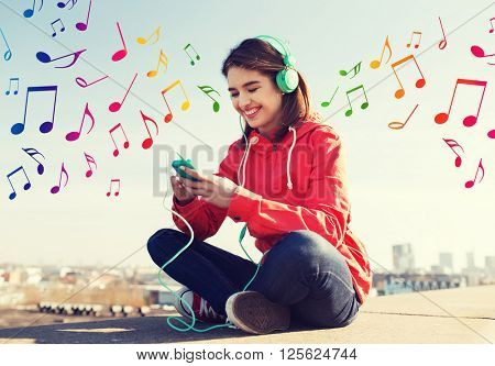 technology, lifestyle and people concept - smiling young woman or teenage girl with smartphone and headphones listening to music outdoors over colorful musical notes background