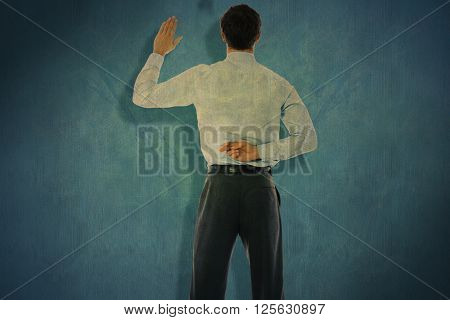 Businessman crossing fingers behind his back against blue