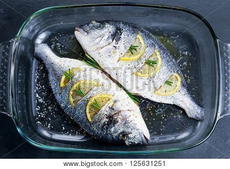 Fresh Raw Sea Bream Fish with herbs. ready to cook in oven. background