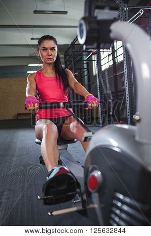 caucasian sporty woman workout on rowing machine in gym
